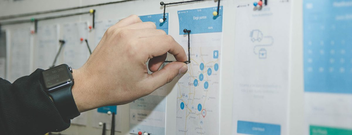 Hand pinning a map on a board
